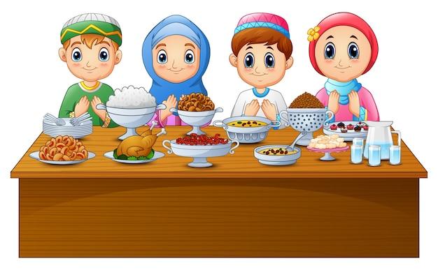 Moslimjong geitje bidt samen vóór onderbreking het vasten Premium Vector