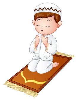 Moslimjong geitjezitting op de gebeddeken terwijl het bidden
