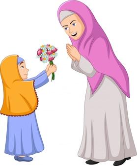 Moslimmeisje dat een bos van bloemen geeft aan haar moeder