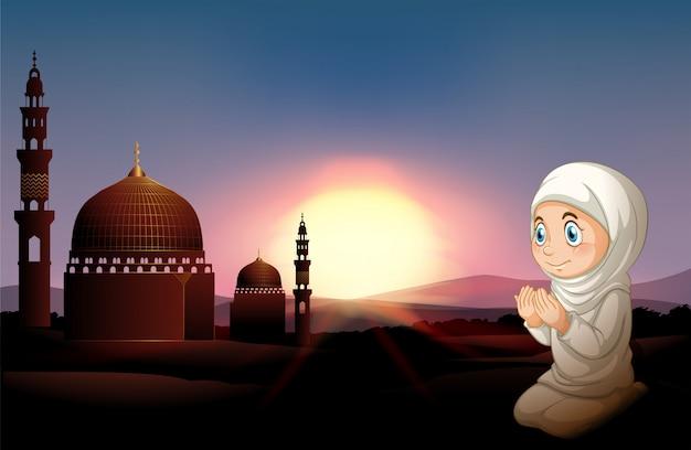 Moslimmeisje die bij de moskee bidden