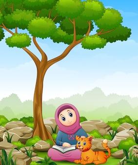 Moslimmeisjesbeeldverhaal die een boek en een kat in de wildernis houden
