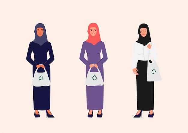 Moslimmensen dragen een stoffen tas voor het milieu en de wereld. geen plastic zakconcept.