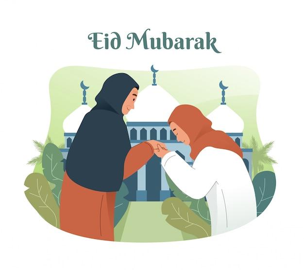 Moslimvrouw die de hand van haar moeder kust. traditie van eid mubarak voor moslims