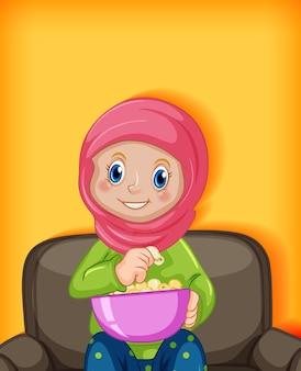 Moslimvrouw die popcorns eet die op bank zitten