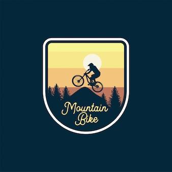 Mountain bike badge jump silhouet gele hemel. logo teken patch ontwerp