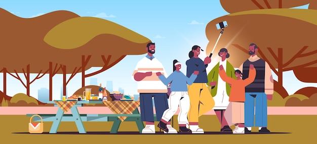 Multigenerationele afro-amerikaanse familie met behulp van selfie stick en het nemen van foto op smartphone camera mensen met picknick landschap achtergrond horizontale volledige lengte vectorillustratie