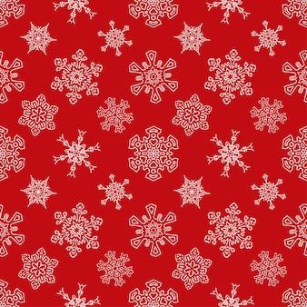 Naadloos kerstmis rood patroon met getrokken sneeuwvlokken