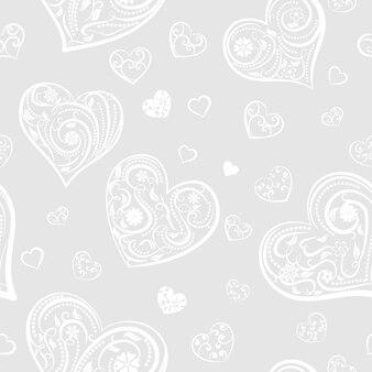 Naadloos patroon van grote en kleine harten met ornament van krullen, bloemen en bladeren, wit op grijs