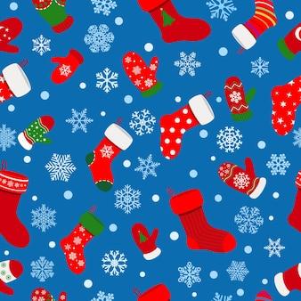 Naadloos patroon van sokken, wanten en sneeuwvlokken op blauwe achtergrond
