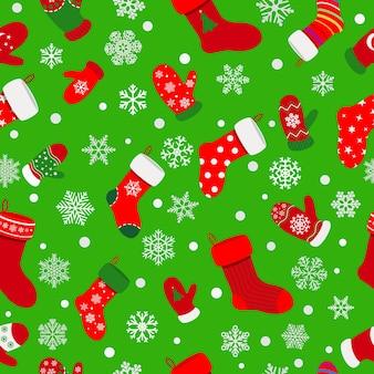 Naadloos patroon van sokken, wanten en sneeuwvlokken op groene achtergrond