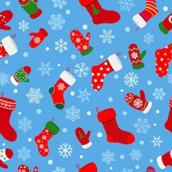 Naadloos patroon van sokken, wanten en sneeuwvlokken op lichtblauwe achtergrond