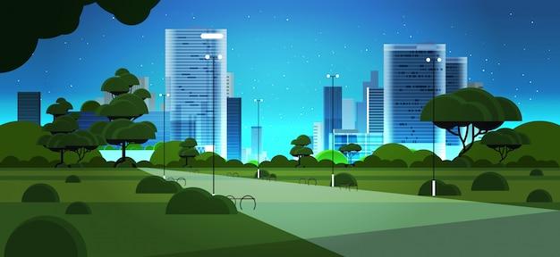 Nacht stadspark stad skyline skyskraper gebouwen en blauwe donkere hemel met sterren stadsgezicht achtergrond