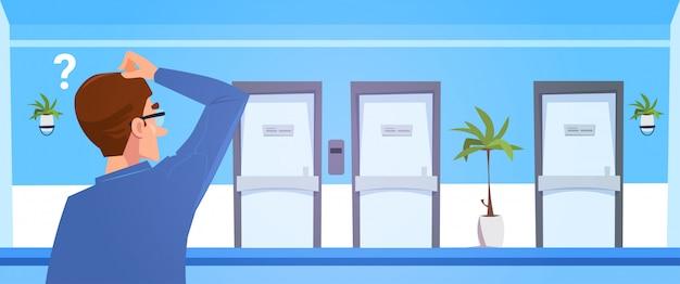 Nadenkende man in het ziekenhuis kiezen van office deur van dortor