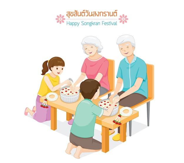 Nakomelingen gieten water op handen van gerespecteerde ouderlingen en vragen om zegen traditie thais nieuwjaar suk san wan songkran vertalen gelukkig songkran-festival