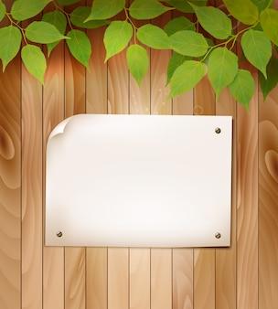 Natuurlijke houten achtergrond met bladeren en een blanco vel papier.