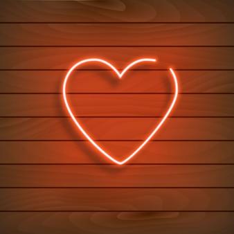 Neon hart. een fel rood bord op een houten muur.