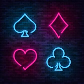 Neon suit poker en casino op bakstenen muur.