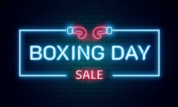 Neon tekst boxing day verkoop op bakstenen muur achtergrond.