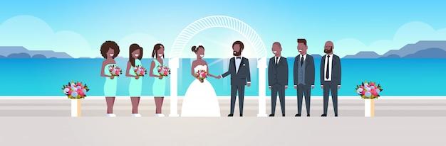 Net getrouwde bruid en bruidegom met bruidsmeisjes groomsmen eendrachtig samen zee strand boog huwelijksceremonie concept zonsopgang bergen achtergrond volledige lengte horizontaal