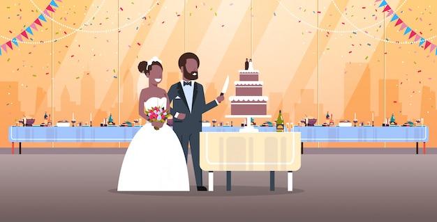 Net getrouwde man vrouw snijden zoete taart romantisch koppel bruid bruidegom verliefd trouwdag concept modern restaurant interieur volledige lengte horizontale flat