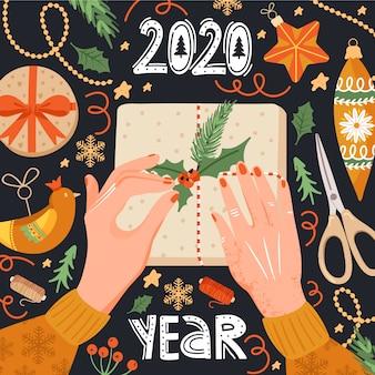 Nieuwjaar 2020-groet met handen die een gift verpakken