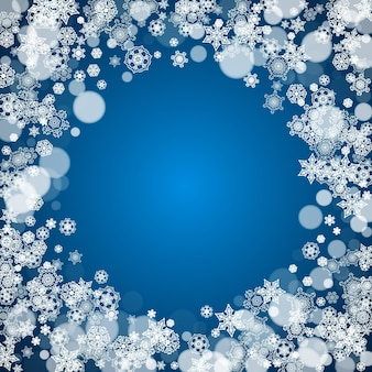 Nieuwjaar frame met koude sneeuwvlokken op blauwe achtergrond. winterraam. kerstmis en nieuwjaar frame voor cadeaubonnen, advertenties, banners, flyers, verkoopaanbiedingen, uitnodigingen voor evenementen. vallende sneeuw en bokeh