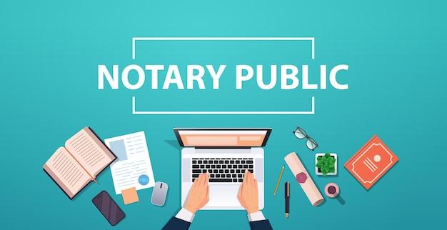 Notaris handen werken aan laptop ondertekening en legalisatie documenten advocaat kantoor werkplek desktop hoek weergave horizontaal