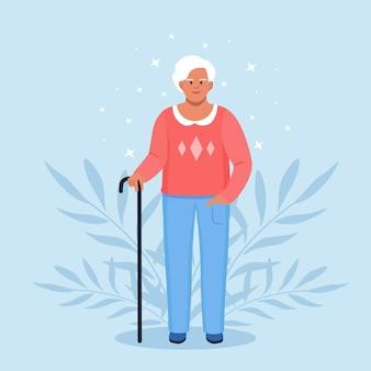 Oma met wandelstok. gepensioneerde, oudere vrouw in casual outfit met stok