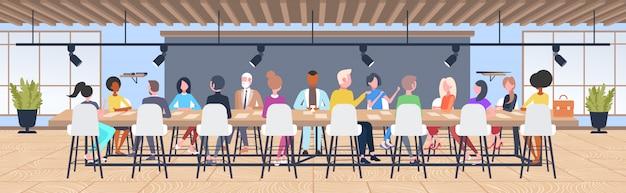 Ondernemers groep brainstormen zittend aan ronde tafel tijdens conferentie bijeenkomst mix race collega's bespreken nieuw project in co-working open ruimte interieur horizontaal