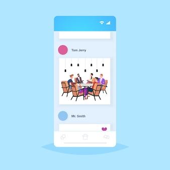 Ondernemers groep vergadering aan ronde tafel collega's brainstormen succesvolle teamwerk concept smartphone scherm mobiele app volledige lengte