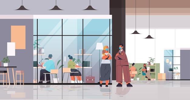 Ondernemers in maskers werken en praten samen in coworking center zakelijke bijeenkomst teamwerk concept
