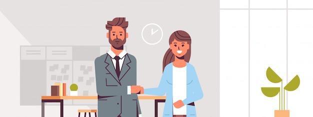 Ondernemers man vrouw handshaking zakenpartners paar handbewegingen tijdens vergadering overeenkomst partnerschap modern co-working center kantoor interieur