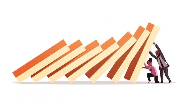 Ondernemers paar stoppen domino-effect crisismanagement kettingreactie financieren interventie conflictpreventie concept horizontale volledige lengte