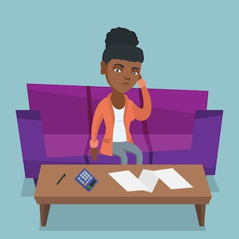 Ongelukkige afrikaanse vrouw die huisrekeningen boekhoudt.