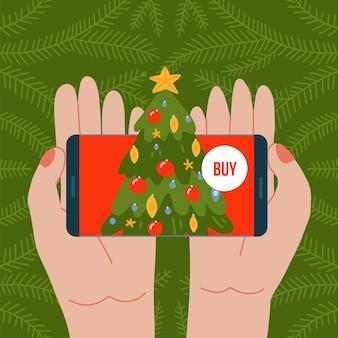 Online kerstboom bestellen twee handen die de telefoon vasthouden met versierde dennenservice voor de levering ...