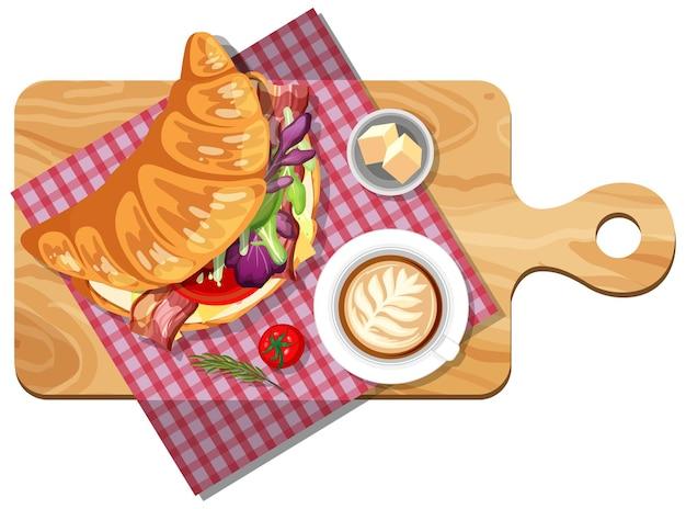 Ontbijtset met croissantsandwich en een kopje koffie op houten plaat
