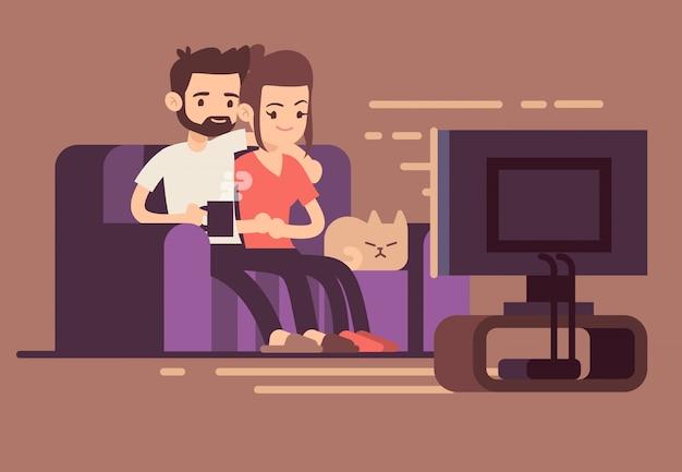 Ontspannen gelukkig jong paar dat op tv thuis in woonkamer let