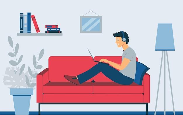 Op de bank zit een man met een laptop. freelancer luistert naar muziek. afstandswerk.