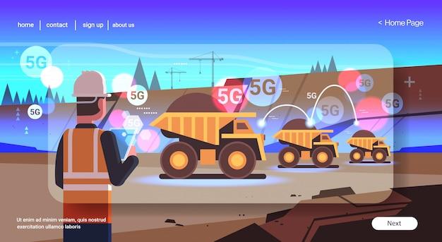 Open pit man met behulp van tablet controlerende dumper vrachtwagens 5g online draadloze systeem verbinding kolenmijn productie open steengroeve achtergrond achteraanzicht portret horizontaal