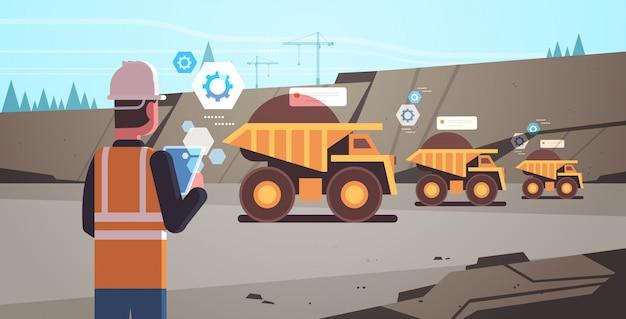 Open pit man werknemer in helm met behulp van mobiele app die dumper vrachtwagens bestuurt