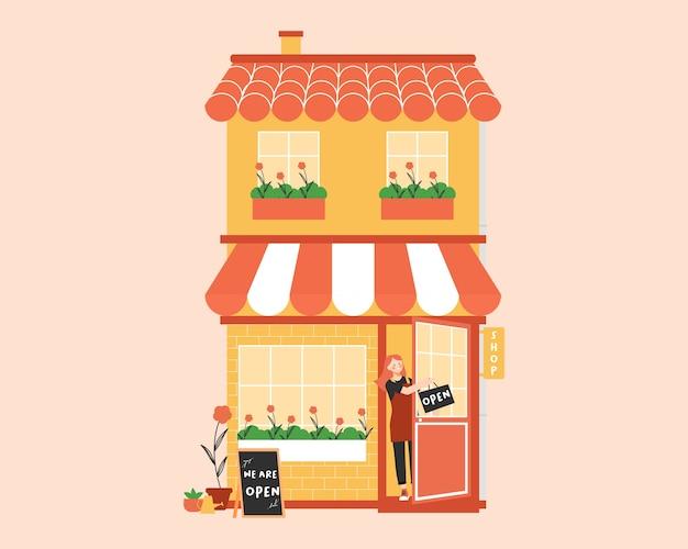 Open winkel met eigenaar van een kleine zakenvrouw of een jonge werknemer die een schort gebruikt en een bord vasthoudt dat zegt dat we open zijn