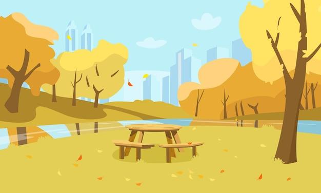 Openbare tuinlandschap met picknicktafel gele bomen rivier- en stadssilhouet