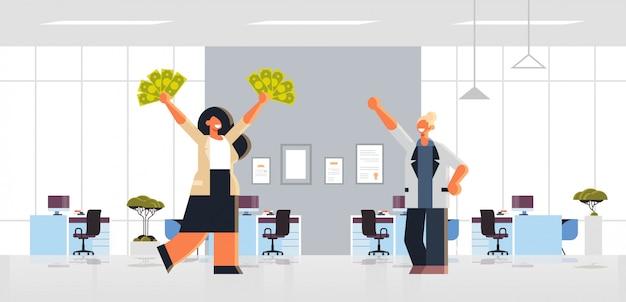 Opgewonden zakenvrouw bedrijf opgeheven dollar contant geld rijke zakelijke vrouwen paar eendrachtig samen financieel succes concept modern kantoor interieur plat volledige lengte horizontaal