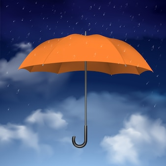 Oranje paraplu op hemel met wolkenachtergrond