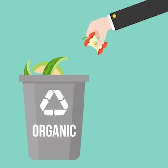 Organisch afval met de hand plukken tot kleurrijke prullenbak