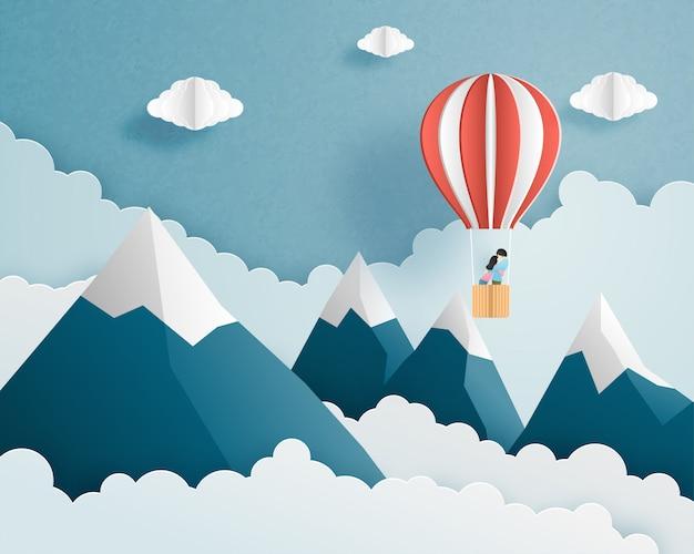 Origami gemaakt paar in hete luchtballon die op wolken en hemel over bergachtergrond en ruimte vliegen.