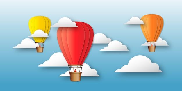 Origami kleurrijke heteluchtballonnen aan de hemel met wolken.