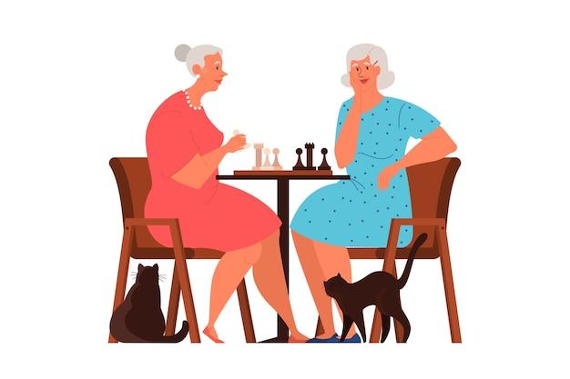 Oude mensen spelen ches. ouderen zitten aan de tafel met een schaakbord. schaaktoernooi tussen twee oude vrouwen.