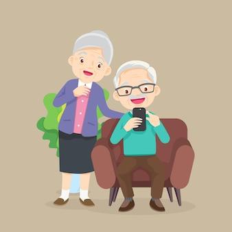 Oudere man en vrouw zitten op de bank en kijken naar de telefoon in de woonkamer