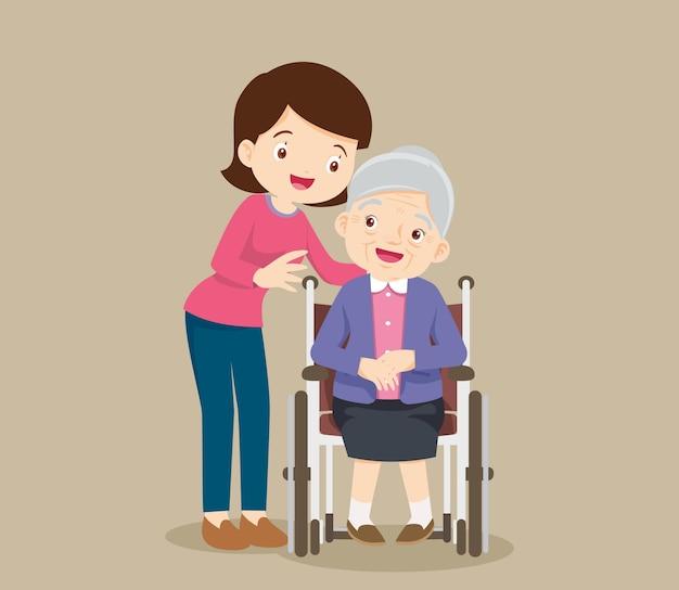 Oudere vrouw zit in een rolstoel en de dochter legt teder de handen op haar schouders.